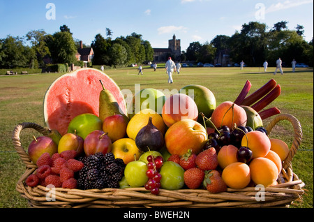 Basket of delicious locally grown fresh healthy summer fruits beside Benenden Village Green with cricket match in - Stock Photo