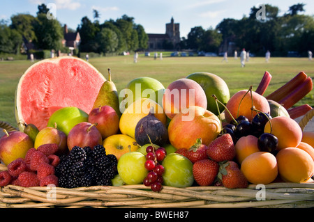 Basket of delicious fresh healthy British summer fruits in basket beside Benenden Village Green with cricket match - Stock Photo