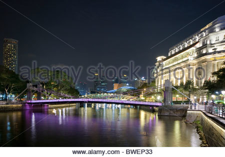 Boat Quay at Singapore River at night with Fullerton Hotel and illuminated Cavenagh Bridge, Singapore, Southeast - Stock Photo