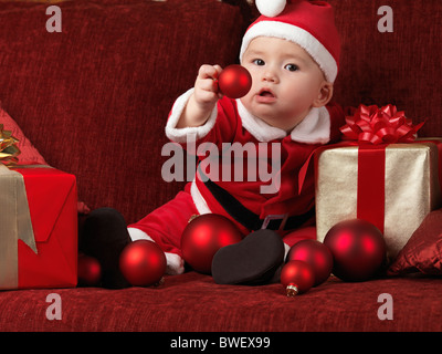Six month old baby boy wearing Santa Christmas costume and holding a red bauble in his hand - Stock Photo
