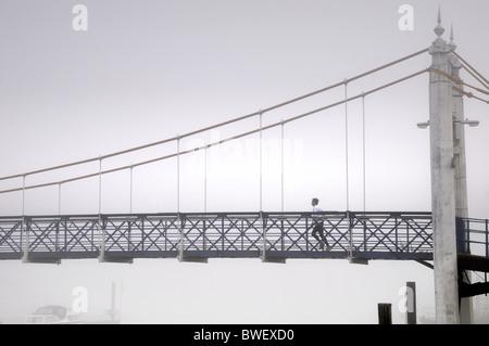 Foggy day at Teddington Lock , West London , with jogger on suspension bridge - Stock Photo