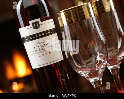 Bottle of red Icewine Cabernet Franc by Hillebrand and two wine glasses in front of a fireplace - Stock Photo