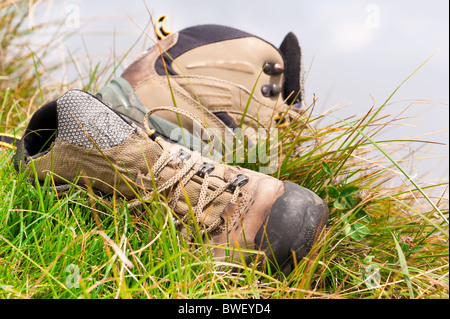 Old hiking boots close-up on green grass - Stock Photo