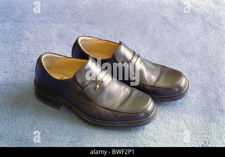 Pair of Clarks Brand Mens Formal Black Leather Shoes on a Blue Carpet - Stock Photo