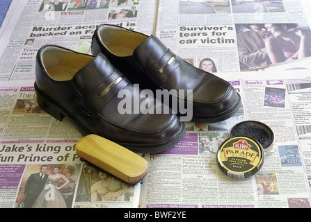 Pair of Clarks Brand Mens Black Leather Shoes on newspaper with Kiwi Brand Shoe Polish and Brush - Stock Photo