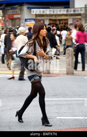 A young woman crossing a street in Shibuya, Tokyo, Japan - Stock Photo