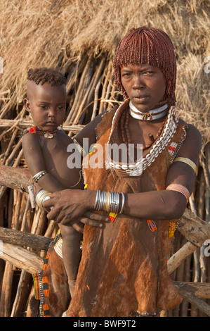Young Hamar woman with necklaces made of Cowry shells and with red clay in her hair holding her baby in the arms, - Stock Photo