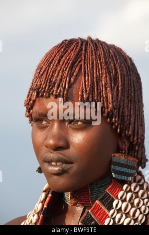 Portrait of a young Hamar woman with necklaces made of Cowry shells and with red clay in her hair, Omo river valley - Stock Photo