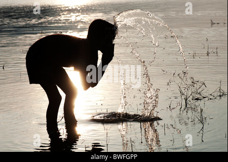Indian boy drinking water and washing in a lake in India at sunset. Silhouette. Andhra Pradesh, India - Stock Photo