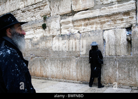 Religious Jews praying at the Western Wall in Jerusalem in the snow. - Stock Photo