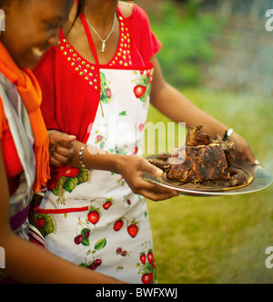 Young ladies serving cooked meat, KwaZulu-Natal, South Africa - Stock Photo