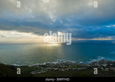 Sunbeams shining through storm clouds onto sea sunset houses Camps Bay in foreground Camps Bay Cape Peninsula Western - Stock Photo
