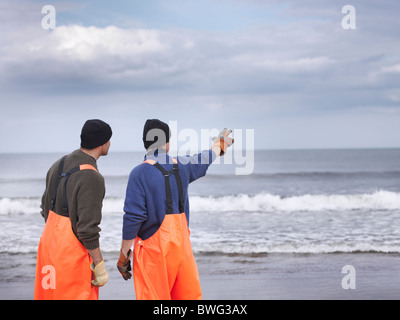 Fishermen on shore pointing out to sea - Stock Photo