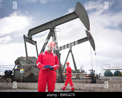 Workers with clipboard next to oil well - Stock Photo