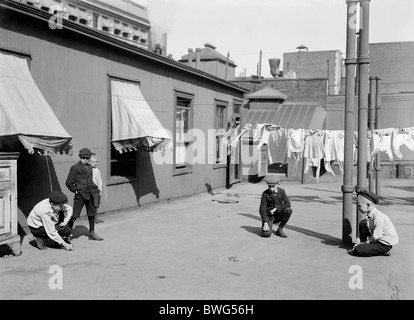 Vintage photo c1910 of young boys playing marbles on the roof of a 'skyscraper' apartment building in New York City.