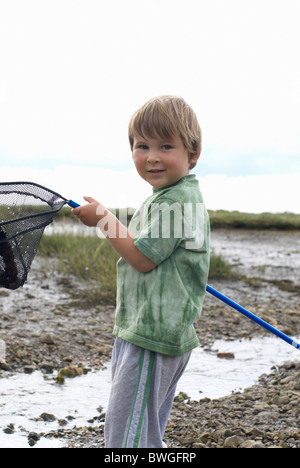 Young boy holding fishing net up - Stock Photo