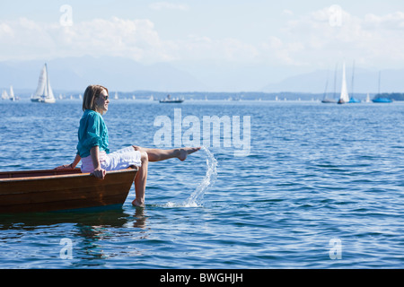 Young woman sitting on a boat - Stock Photo