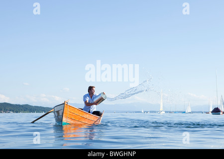 Throwing buckets of water ot ouf boat - Stock Photo