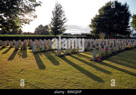 Sunset over sunlit headstones in the Commonwealth War Graves Cemetery in Bayeux, France. - Stock Photo