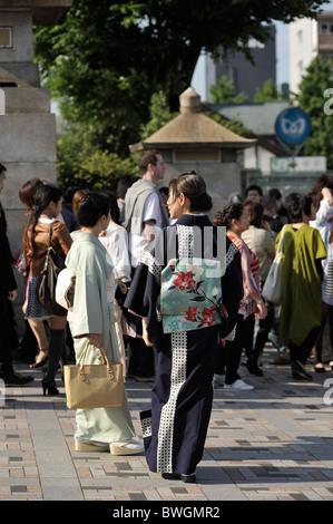 Two young Japanese women in traditional Geisha-like outfits on crowded Jingu bridge, Harajuku, Tokyo, Japan - Stock Photo