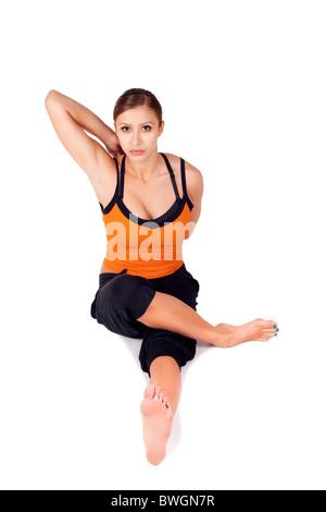Fit beautiful woman doing yoga exercise called Gomukhasa Paschimottasana, isolated on white background - Stock Photo
