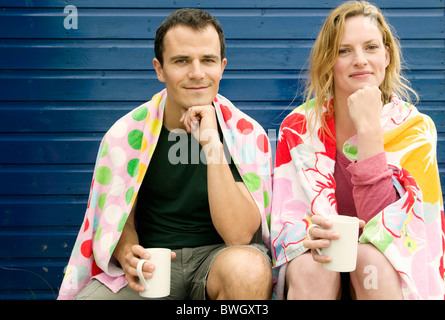 Couple relax with hot drinks on beach - Stock Photo