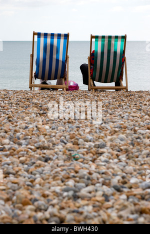 England, West Sussex, Bognor Regis, Two elderly seniors sitting on deck chairs on the pebble shingle beach looking out to sea.