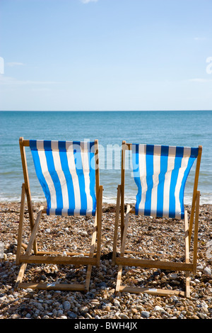 England, West Sussex, Bognor Regis, Two blue and white deck chairs on the shingle pebble beach looking out to sea.