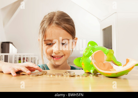 Little girl counting money - Stock Photo