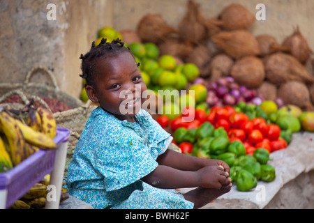 Little girl at a fruit and vegetable stand on Lamu Island, Kenya - Stock Photo