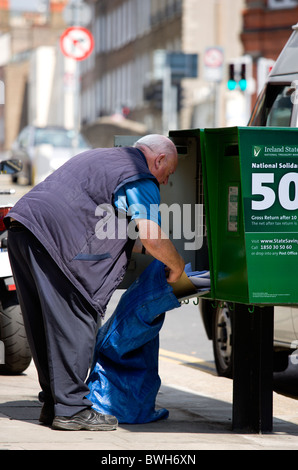 Ireland County Dublin City Post Irish postal worker emptying mail from green modern letterbox into sack on pavement - Stock Photo