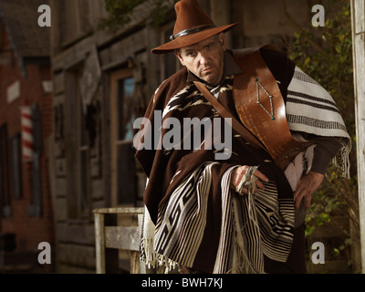 Cowboy sitting on a handrail with old wooden houses in the background - Stock Photo