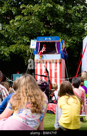 Children, Entertainment, Punch and Judy Show, Children sitting on grass watching the traditional puppet show. - Stock Photo