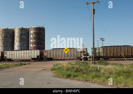 Freight train rolls along tracks in rural area along US Highway 287 in the Panhandle portion of Texas, USA - Stock Photo