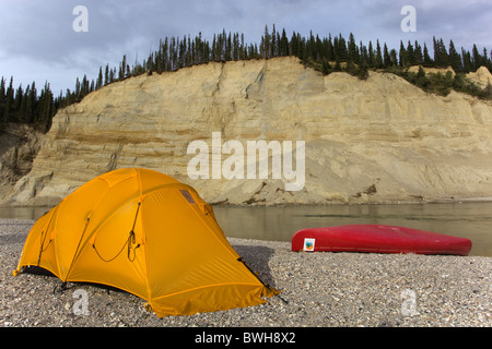 Camp, tent and canoe on a gravel bar, high cut bank, river cliff, erosion, behind, upper Liard River, Yukon Territory, - Stock Photo