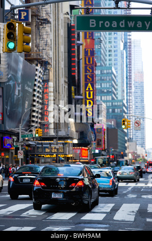 USA, New York, Manhattan, Cars crossing Broadway at green traffic lights travelling east along 42nd Street in Theatre - Stock Photo