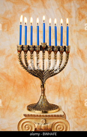 Menorah with blue candles on pedestal - Stock Photo