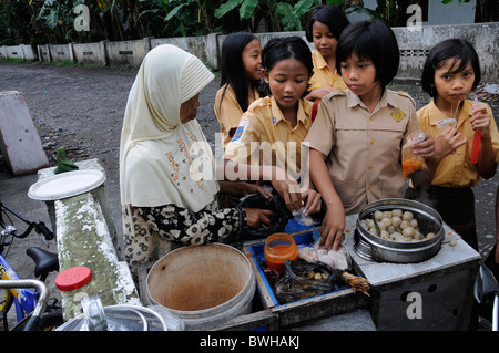 Pupils in school uniform during the break in front of the school at a Muslim hawker, Yogyakarta, Central Java, Java, - Stock Photo