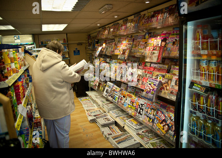 A woman browsing magazines in a small local newsagents shop UK - Stock Photo