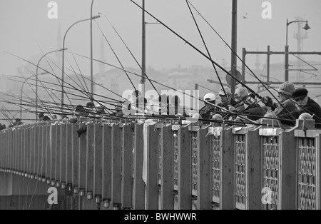 ISTANBUL, TURKEY. Men fishing in the Golden Horn from the Karakoy end of the Galata Bridge. 2010. - Stock Photo