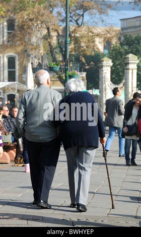 ISTANBUL, TURKEY. An elderly couple walking arm in arm in the Bosphorus suburb of Ortakoy. 2010. - Stock Photo