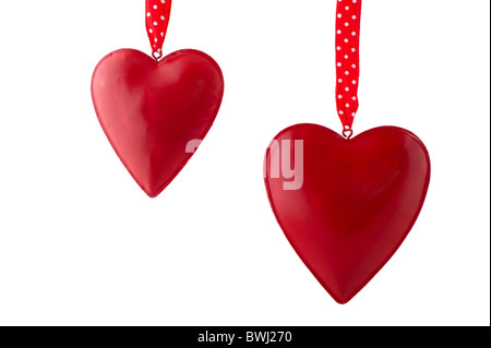 Two read hearts hanging in front of a white background - Stock Photo