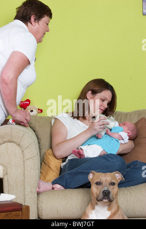 Maternity nurse helping mother with formula milk bottle feeding newborn baby on the sofa - Stock Photo