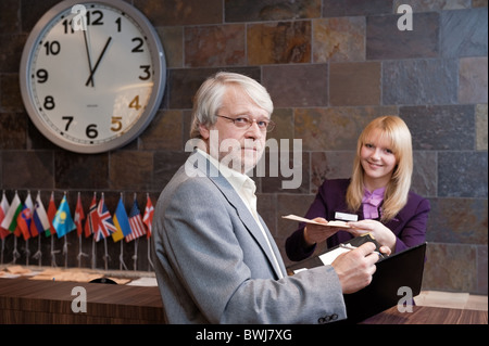 Businessman checking in at the reception desk - Stock Photo