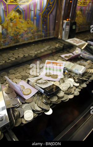 gambling machine game with coins and prizes in casino amusement arcade in uk - Stock Photo