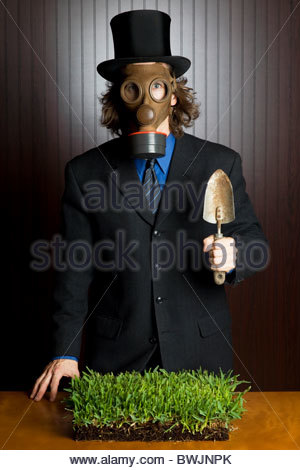 Businessman wearing a gas mask holding a potting shovel standing over a patch of grass - Stock Photo