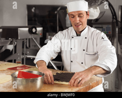 Portrait of a baker making pastries with poppy seeds in a bakery - Stock Photo