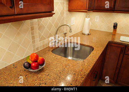 Stainless steel sink in a remodeled kitchen with a quartz counter - Stock Photo