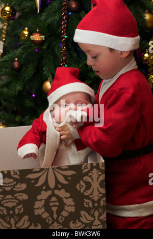 Little boy dressed up like santa unpacking his christmas gift, which is a little baby brother, also in santa clothes. - Stock Photo