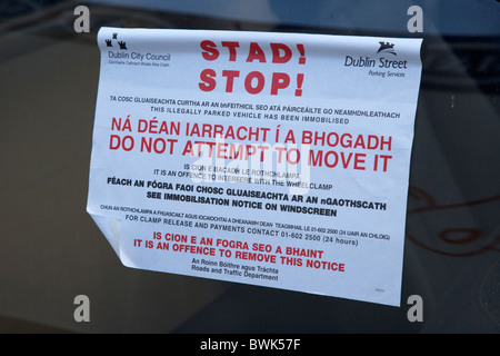 bilingual stop warning sign in gaelic irish and english for parking violation in Dublin republic of ireland - Stock Photo